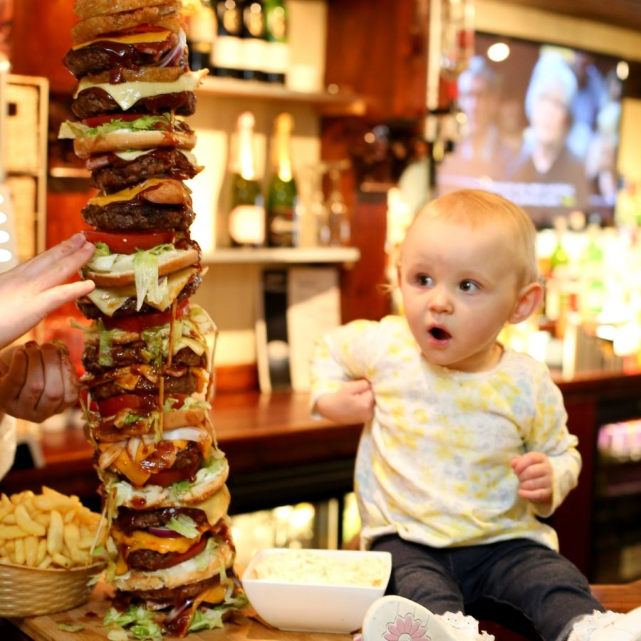 One year old Isla, who inspired Craig Harker's attempt at the UK's tallest burger looks bemused as she sits on the bar next top the 28 inch high meal. See SWNS story SWBURGER; A restaurant owner has created the daddy of all meals - Britain's tallest burger which is bigger than his DAUGHTER. The whopping two-and-a-half-foot '999 burger' is higher than Craig Harker's toddler and trumps the previous UK record by several inches. It gets its name from the 30,000 calorie content - enough to feed one person everyday for TWO WEEKS - which could leave any diner dialling for an ambulance. Regulars at The George in Stockton, Teeside, have been giving owner Mr Harker a big patty-on-the back for the 28 inch culinary masterpiece.