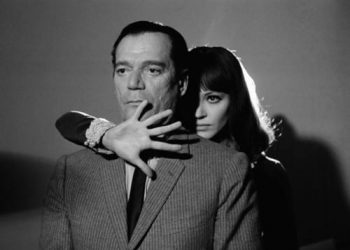 """1965, France --- American actor Eddie Constantine and Danish actress and singer Anna Karina on the set of """"Alphaville, Une Etrange Aventure de Lemmy Caution"""" (Alphaville, a Strange Adventure of Lemmy Caution) by her husband French Swiss director, screenwriter and producer Jean-Luc Godard. --- Image by © Georges Pierre/Sygma/Corbis"""