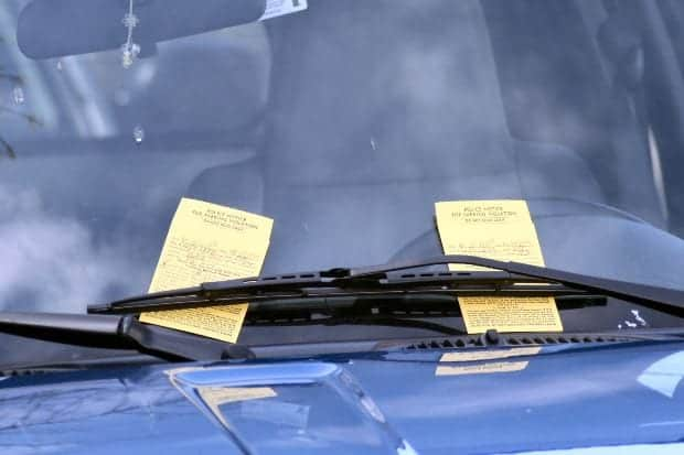 Two parking tickets, tucked beneath a single windshield wiper, await a likely angry driver when he returns to his vehicle on a street in downtown Doylestown PA. 2008-04-05.