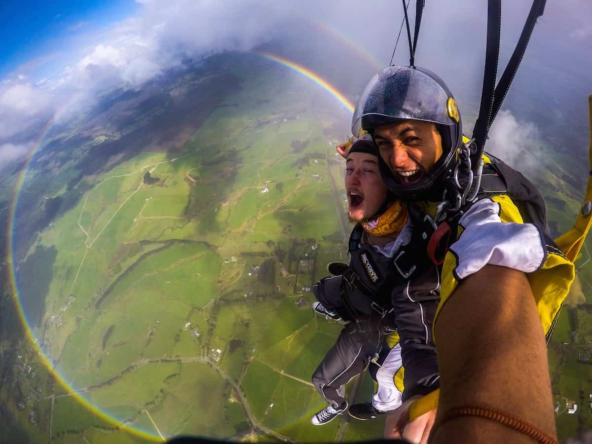 """Anthony Killeen gets the thrill of his life as he skydives over a 360 degree rainbow. See SWNS story SWRAINBOW;  The British expat was on his first skydive with an instructor over New Zealand's Bay of Islands when he spotted the perfect circles of colour. Killeen said the rainbow kept its form until it was time to descend and land. """"All the instructors said they hadn't seen that before either - some had seen it from the plane, but never whilst diving."""""""