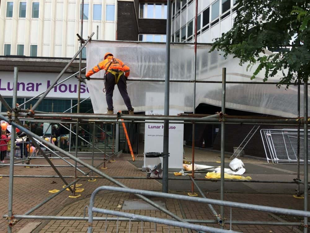 """Construction workers were seen erecting 15ft scaffolding in front of a Home Office building, ahead of the latest arrival of """"child refugees"""" from Calais to London. See NATIONAL story NNMIGRANT. Yesterday another 14 migrants arrived in Croydon, with half asking not to be photographed and many covering their faces with towels. Today, around half a dozen construction workers were seen building a structure which appeared to be the foundations of a screen. A construction firm employee confirmed it was a last minute job, organised this morning. The structure reached around the area where all previous coaches from Calais have stopped outside Lunar House, the Home Office building where migrants are interviewed. The labourers were employed by the firm Phoenix Scaffolding. An employee from the firm, who didn't wish to be named, said: """"All I know is that it was a last minute job. """"We were called up quite early this morning. """"I don't know what it is or who called us."""" The Home Office has been contacted for a commented."""