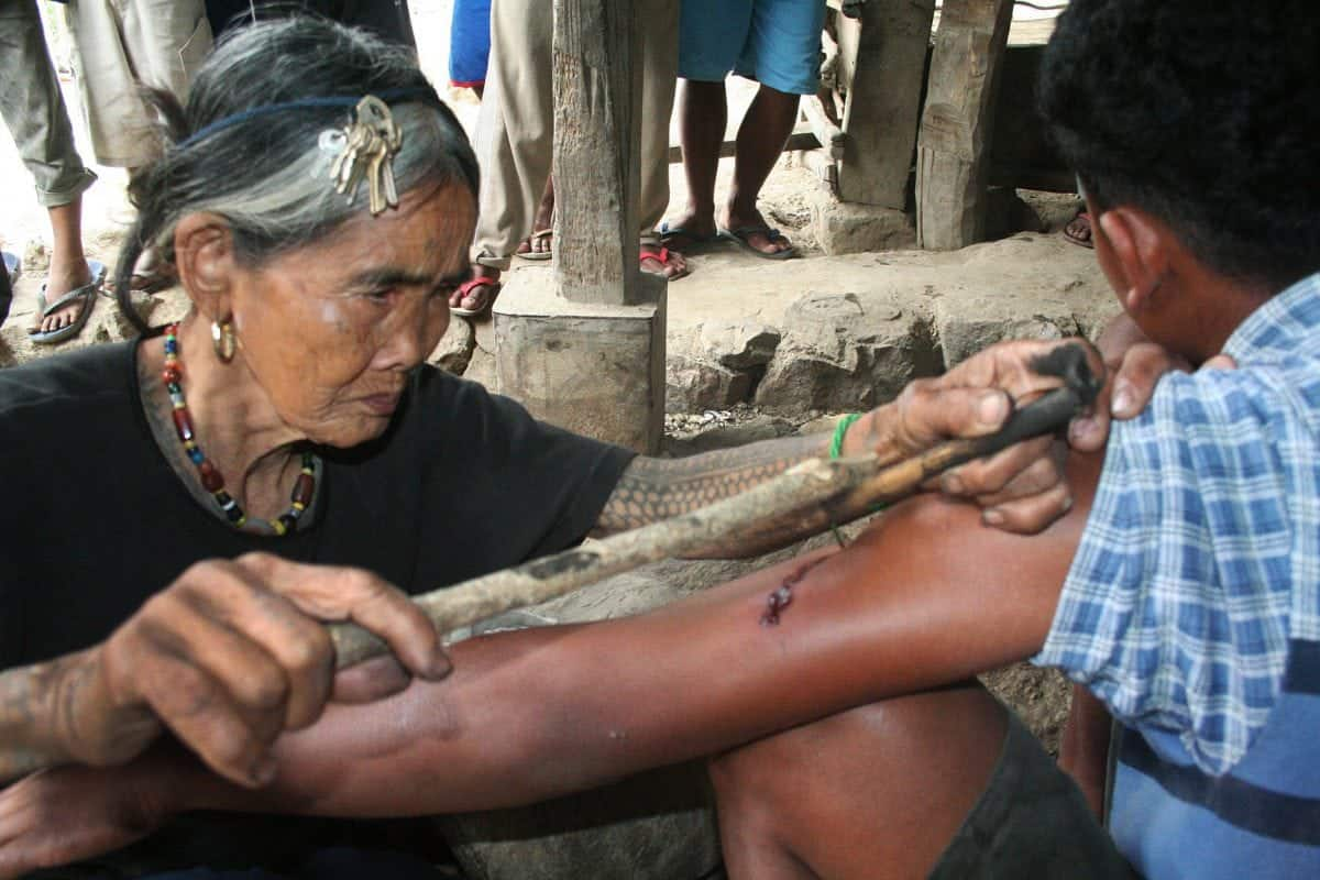 Meet the world's oldest tattooist whose tribal inkings are 20 TIMES more painful than normal body art. See SWNS story SWTATT;  Filipino spinster Whang-od, 97, dedicated her life to tattooing villagers since she learned the ancient practice aged just ten. She uses charcoal and water to make the ink, which is then hammered inside the skin using a THORN from a tree. Hundreds of 'tattoo tourists' a year now trek to her remote mountain village in Kalinga province, some ten hours from the Philippines capital Manilla, for one of her ancient designs.