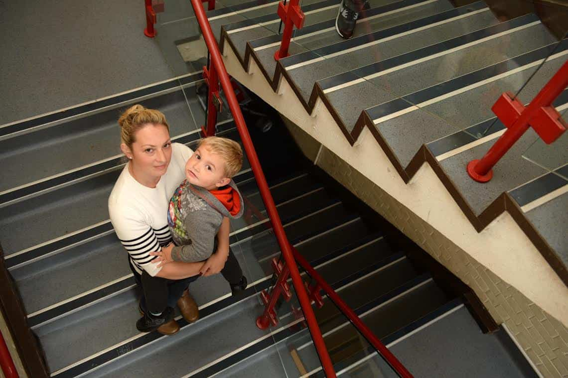 Sharon Arkell with her son Tommy, 3 on the stairs which lead to their council house. See SWNS story SWSTAIRS; Council housing chiefs saw a video of a mum struggling to carry her four-year-old with muscular dystrophy up two flights of stairs – and turned down a request for priority housing because she made it to the top. A panel at South Gloucestershire Council watched the news film of Sharon Mikkelson carrying her son Tommy up the 30 stairs to their second-floor flat in Filton as part of a hearing to decide whether the family qualified to be awarded priority housing status. Young Tommy will soon receive his first wheelchair next week as the muscular dystrophy which is already affecting his body gets worse. The family have asked to be re-homed in a ground floor flat or home, but have not been offered anything suitable.