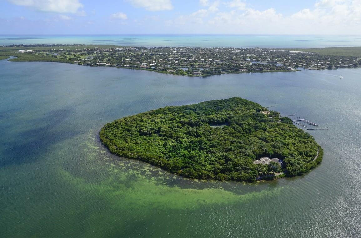 """This 26 acre tree-covered private island with marina and beach has been put on the market for £75 MILLION. See SWNS story SWISLAND; Pumpkin Key is an """"extraordinary"""" retreat which boasts a three-bedroom main home, two caretaker's cottages and a dock master's apartment. It also has a 20-slip marina which is large enough to accommodate a megayacht. The island, which is a ten-minute helicopter ride from Miami's famous South Beach, has panoramic views of Card Sound Bay and spectacular sunsets."""