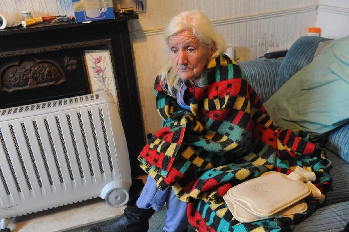 """Pictured is Shirley Walsh at her home on Kathleen Road, Hull, where she is forced to use electric heaters, hot water bottles and blankets to keep warm. See Ross Parry story RPYCOLD; A 74-year-old widow has been left """"freezing"""" in her Hull home for months after her gas was cut off leaving her with no central heating or hot water. Shirley Walsh, from east Hull, takes SIX hot water bottles to bed with her at night in a desperate bid to keep warm. The retired seamstress says her supply was cut off in September after workmen found a leak in pipes under her front garden in Kathleen Street, where she has lived for 43 years. But because the leak was on her property, Northern Gas Networks told her she would have to pay for the repair, a cost the pensioner says she can't afford."""