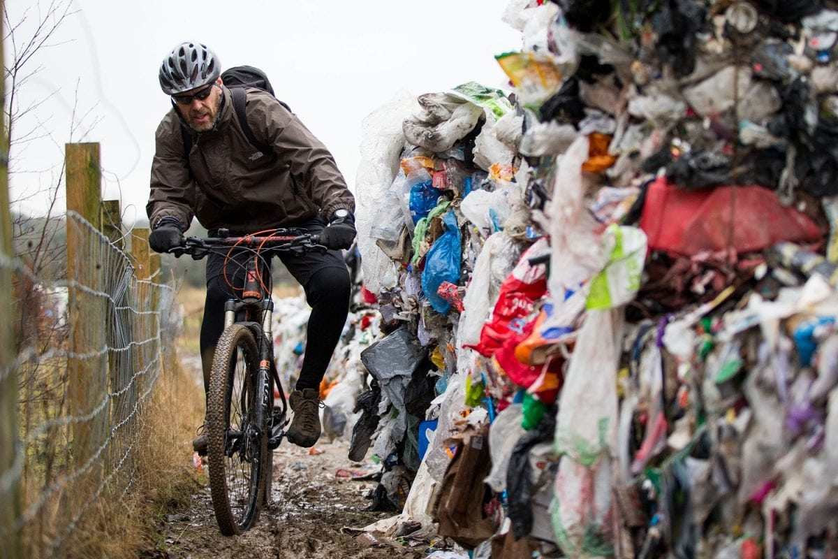 """Lee Tanner 49 rides past a mountain of waste such as food products, plastics and paper has been dumped on a cycle path between Biddulph and Brindley Ford, Staffordshire. February 01, 2017.  See NTI story NTIRUBBISH; Police are hunting """"industrial fly-tippers"""" who dumped 50 huge blocks of compressed recyclable rubbish at a beauty spot popular with mountain bikers and walkers. Tens of thousands of discarded plastic bottles, bags and cardboard boxes which had been compacted into 10ft-high cubes were left strewn across the path. Cyclists and walkers were forced to squeeze past the stinking piles of trash after they were discovered on the route between Biddulph and Brindley Ford, Staffs., on Saturday (28/1).  Staffordshire Police and council officials are now investigating in a bid to find out who dumped the rubbish. Dog-walker David Rowe, 66, who discovered the waste, said: """"I walked my dog on Friday night and there was nothing there."""