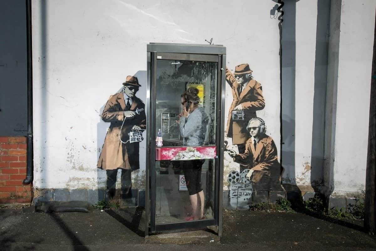 """FILE PHOTOS OF phone box which has been surrounded by new Banksy artwork in Cheltenham. 14th April 2014. See SWNS story SWBANKSY; A famous Banksy once valued at a million pounds which """"fell"""" off a wall appears to be for sale on Facebook. The elusive artist created 'spy booth' depicting three 'spooks' snooping on a phone box with listening devices near GCHQ in Cheltenham, Glos., in 2014. But it was reduced to a pile of rubble when builders worked on the wall above the artwork and it collapsed last summer. Building owner David Possee took the bits to the council for safekeeping, but yesterday (Weds) the broken pieces appeared for sale on Facebook."""