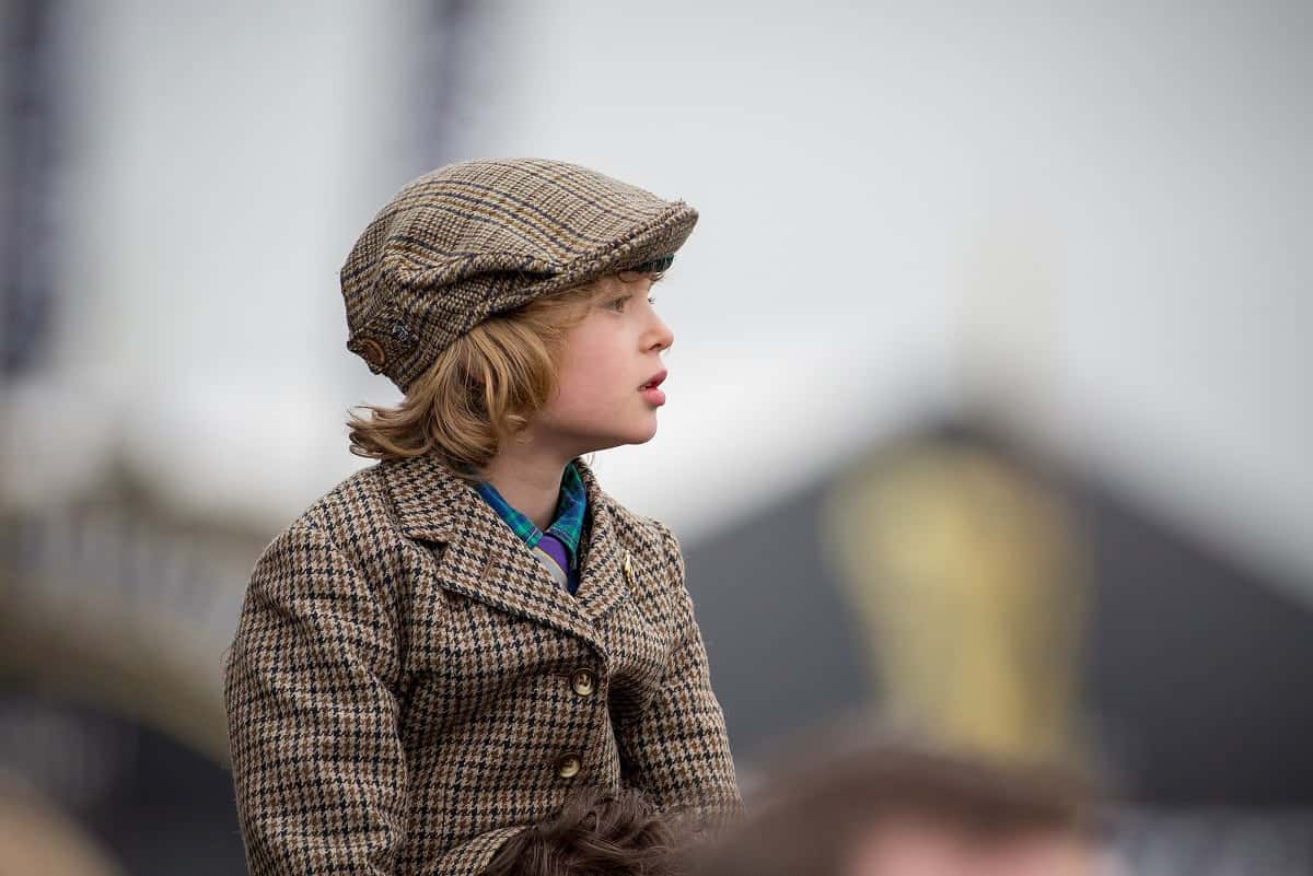 A young boy watches the third race of the day at the Gold Cup, the final day of the horse racing, at the Cheltenham Festival 2017, which is also St Patrick's Day. March 17 2017.
