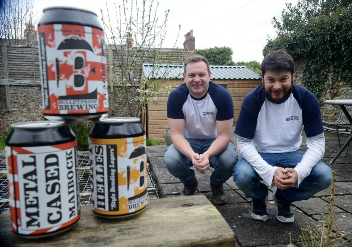 """Patrick Lawrence (right) and Connor Johnson who run a micro brewery business from a garden shed. See SWNS story SWSHED; It gives the term beer garden a whole new meaning - Plymouth's newest microbrewery is in a backyard shed. The Bulletproof Brew Co has been created in the back garden of liquor entrepreneur Patrick Lawrence's mum's city centre house. And it's pumping out 400 litres of German-style craft lager every week. That's 1,200 """"stubby"""" 330ml cans – the container of choice for the emerging craft beer industry. Mr Lawrence and co-director Connor Johnson now want to grow the one-year-old firm – because they are already having problems meeting demand."""