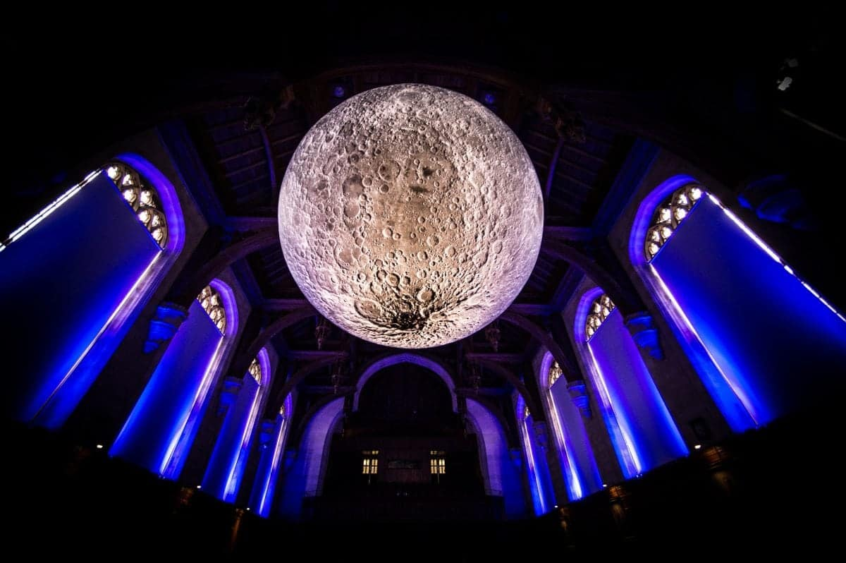Artist Luke Jerram with his installation, Museum of the Moon, in the University of Bristol Great Hall, Wills Memorial Building, Bristol. See SWNS story SWMOON; Measuring seven metres in diameter, Luke's Moon features detailed NASA imagery of the lunar surface. Each centimetre on his moon represents 5km on the surface of the Earth's largest natural satellite. The installation in the Great Hall is part of the Moon's international tour in which it is presented in different ways, both indoors and outdoors, altering the experience of the artwork for different audiences worldwide.
