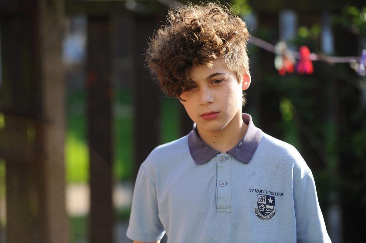 """Haman Karim, 13, has been kept in isolation for two months at St Mary's College because of his haircut. See Ross Parry story RPYPERM; An angry mum claims her teenage son has been taken out classes after having his hair PERMED to copy his rapper idol. Haman Harim, 13, had his head shaved at the sides and an 80s-style perm on top so he could look like teen rapper Little T. But mum Sharon Coxall says he was then excluded from normal classes because teachers claimed his retro hairstyle was affecting his education. Sharon, 51, hit out at the decision by teachers to put him in 'pastoral' care over his hairdo two months ago. And she claims that even though the shaved sides have now grown out the school are still keeping the Year Nine pupil 13 out of mainstream classes. The mum-of-six blasted: """"It's a bit over the top. How does his hair affect his education? That's what is important."""""""