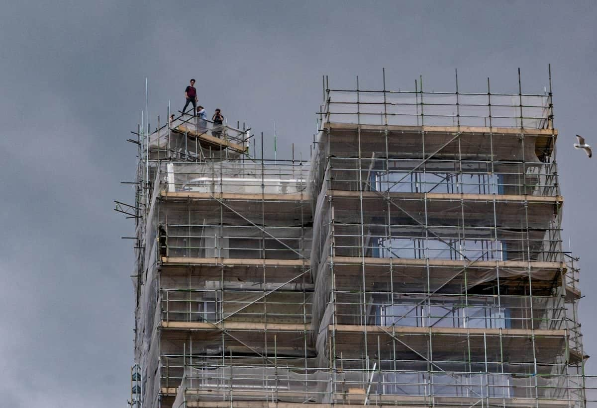 """One of the astonishing pictures of youths who had scaled one of the tallest buildings in the south west and were seen posing pricariously at the top. See SWNS story SWSTUNT; A group of young people have scaled one of the tallest buildings in the South West, which is currently under construction. The 22-storey, 78m-high (256ft), Beckley Point building in Plymouth, is due to be occupied by university students from September. It is unclear whether the group was """"rooftopping"""" - climbing to the top of structures to take photographs. Devon and Cornwall Police said it was aware of the incident."""