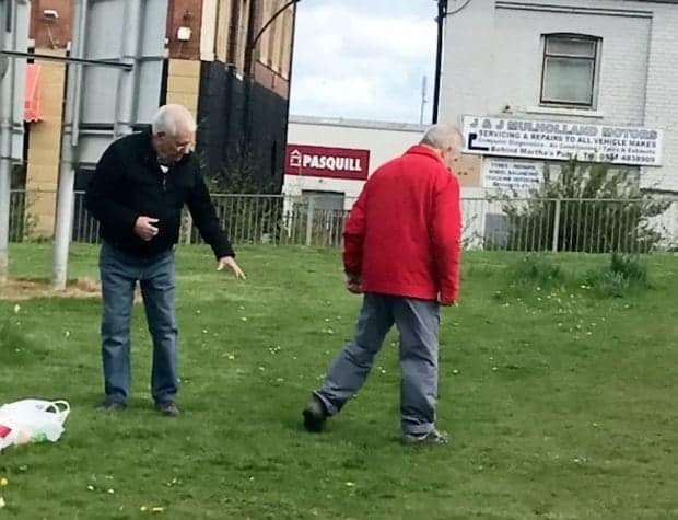"""**ONLINE EMBARGO UNTIL MIDDAY, APRIL 19, 2017** This is the funny moment two OAPs settled an old score with a fist fight outside a care home - before one helps the other look for his glasses.  See SWNS story SWFIGHT.  Onlookers said the pair crossed paths with one accusing the other of """"ignoring him for months"""".  The argument got heated - with the pair both setting down the carrier bags - before they squared up to each other with the fists clenched on a nearby green.  A video taken by a baffled passerby, shows the pair with their arms raised, throwing and landing punches outside the Hawthorn Court care home in Hebburn, Tyne and Wear.  The man in the black jacket can be seen pointing and ranting, before his opponent punches him.  But after a few fists fly, they both stop to find a pair of specs belonging to the man in red - apparently knocked off by the first punch."""