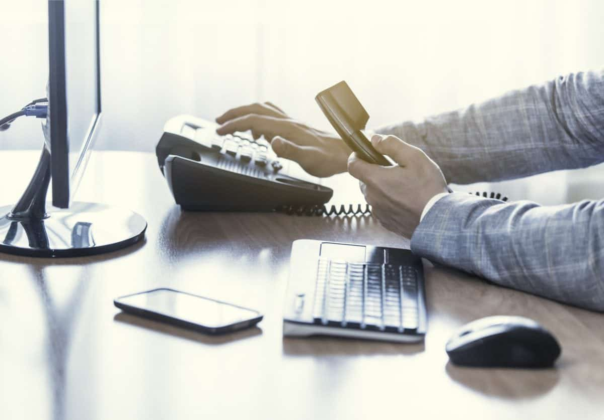 Businessman use the phone in the office, keyboard, mouse, mobile, and monitor detail in the background
