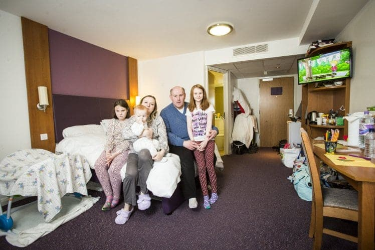 """***EMBARGOED UNTIL 3.00PM GMT*** Luke and Olga Burns, with their children  Lolita (brown hair), 11, Alina, 10, and Nicolas, 11 months. The family have been forced to live in hotels for nearly three years after the council failed to find them a house. See SWNS story SWHOTEL; A council has been ordered to rescue a homeless family-of-five after leaving them """"trapped"""" living in a hotel for THREE YEARS - at a staggering cost of £88,000. The Burns moved into a hotel when they were turfed out their flood damaged private rental flat in 2014 and thought they would be there for a week. But two authorities spent months arguing over who should look after them before they were declared """"intentionally homeless"""" - putting an end to any council help. Since April 2014 Luke Burns and his wife Olga - both qualified teachers - have been forced to limp from handout to handout to keep a roof over their heads."""