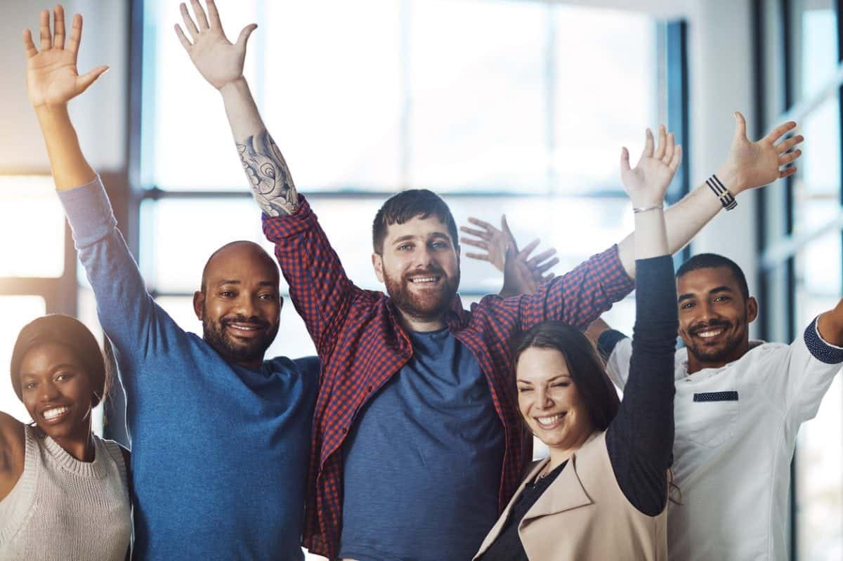 Portrait of a group of young colleagues cheering at work