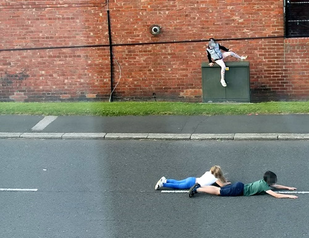These shocking photographs show children dicing with death as they dodge cars by lying in the middle of a busy ROAD. See ROSS PARRY story RPYCHICKEN.  The three children appear to be playing 'chicken', a game involving waiting as long as possible in the way of cars, before jumping away at the last second.  In one of the images, two of the children are seen lying in the middle of the road, while another image shows one the children running out on to the road as a car speeds past.  The photographs, which were taken in Washington, Tyne and Wear, were sent to police by local councillor Dianne Snowdon after local residents raised concerns.  Officers from Northumbria Police are working to identify the children in the images so their parents can be spoken to about their reckless behaviour but police also want to remind people of the dangers of playing on and near busy roads.