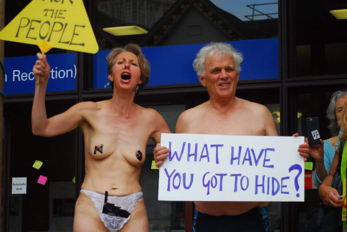 """Two campaigners stage a nearly naked proest outside Shire Hall in Gloucester where plans for an incinerator have caused outrage amongst residents. See SWNS story SWPROTEST; Semi-naked activists have staged a protest outside Shire Hall in Gloucester in an attempt to reverse a decision on the controversial incinerator. The small group brandished placards outside the building yesterday afternoon in what is the latest episode in the long-running battle with the county council over the construction. As well as putting post it notes on the windows of the building, two protestors bared all for the cause, wearing nothing but pants and one had tape over her nipples. One carried a sign saying """"What have you got to hide?"""""""