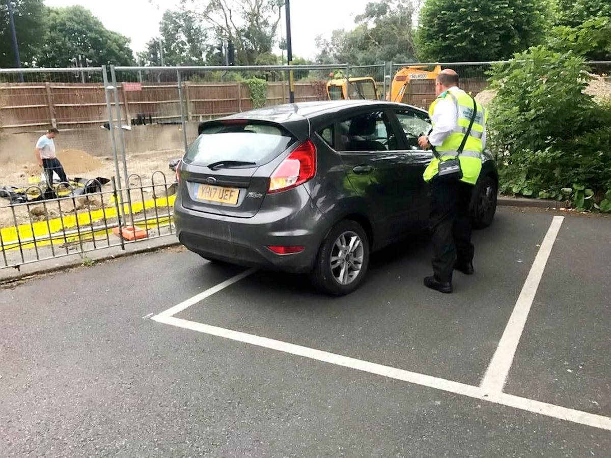"""Baffled residents were left outraged after a parking warden left his car carelessly across half a bay - and say he should have given himself a ticket.  See NATIONAL story NNPARK.  A picture snapped by local Steven Way shows the enforcement officer's shoddy parking outside the white lines, although not obstructing other cars.  The grey 17-plate Ford Fiesta, driven by a Shepway District Council warden, was spotted in Hythe, Kent, on Monday morning.  Steven, a chartered building surveyor, stressed that the officer """"shouldn't need to be told"""" how to park correctly in the bay."""