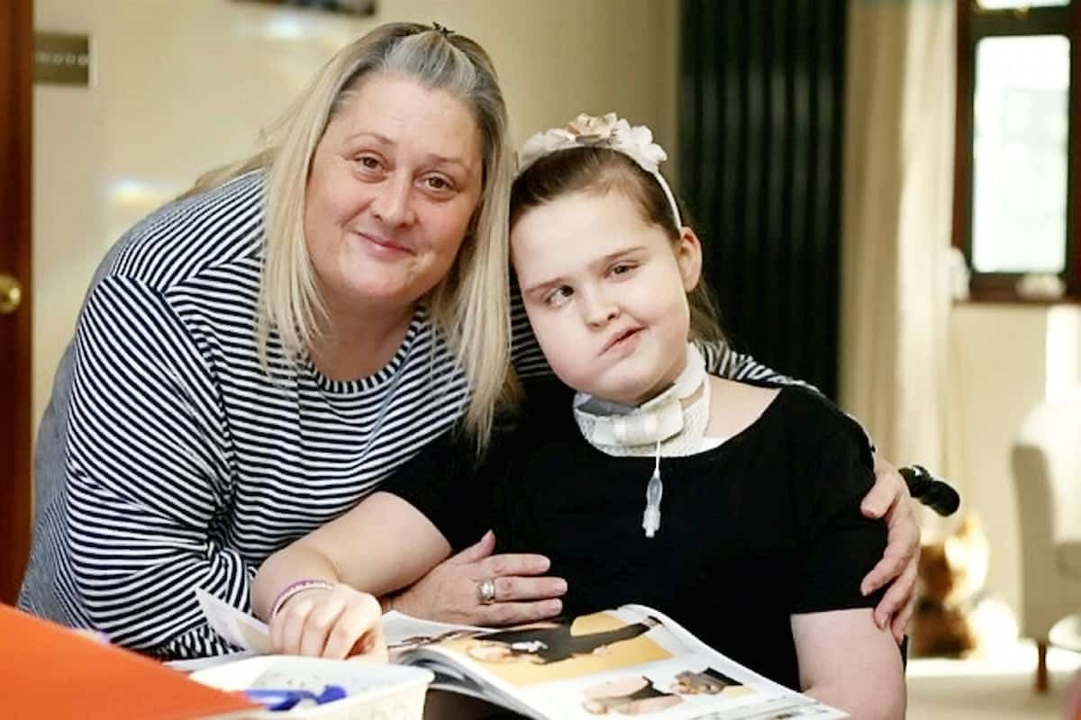 """Emma Garbutt and her daughter Millie.  A young girl who lost her voice after brain tumour surgery can now only communicate using her iPad - and SIRI. See NATIONAL story NNIPAD.  Millie Garbutt was left unable to speak after having a life-saving tracheotomy after doctors operated on a brain tumour.  Now the 12-year-old has to communicate using the text-to-speech function on her tablet computer - that uses the same voice as Apple's 'virtual assistant' Siri.  Mum Emma Garbutt said: """"She has an iPad and another electronic device which attaches to her wheelchair and helps her communicate with everyone."""