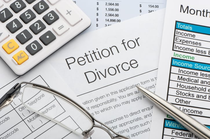 Close up of a petition for divorce with pen and calculator