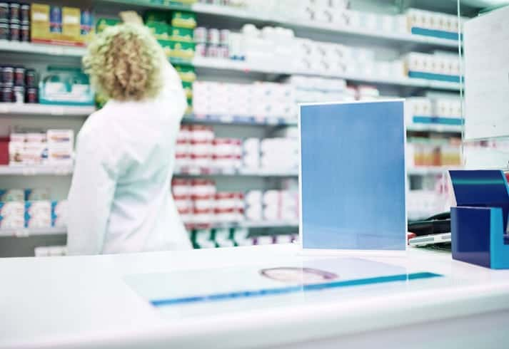 Shot of a blank board on the counter of a pharmacy with a pharmacist working in the background
