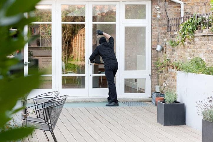 Burglar standing at patio door