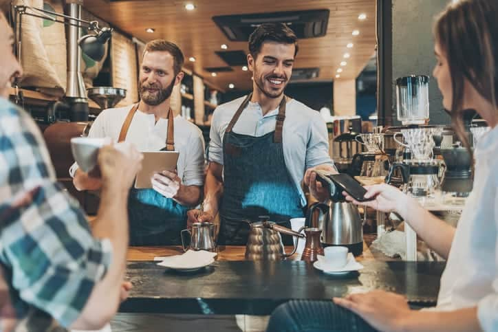 Smiling barista with barcore reader accepting smart phone payment