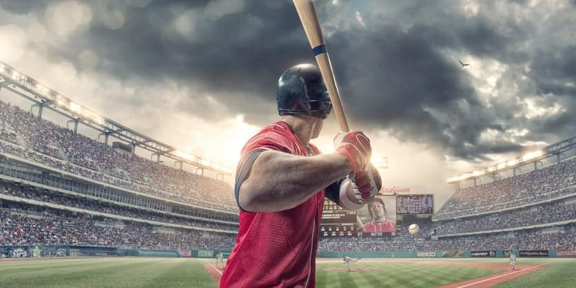 A close up rear view of a professional male baseball player wearing a red baseball strip and safety helmet, holding baseball bat just about to strike incoming baseball. The action occurs during a baseball game in a generic floodlit outdoor stadium full of spectators. Baseball ground, scoreboard etc are all fictional.