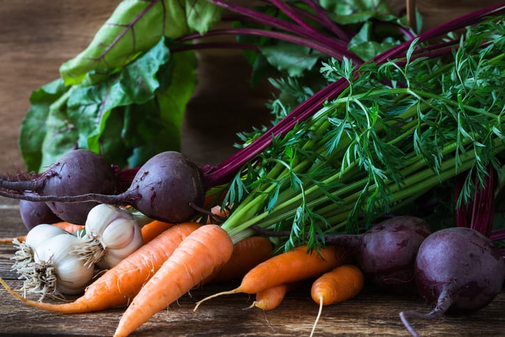 Bunch of fresh organic beetroots, garlic and carrots on wooden rustic table, different types of root vegetables