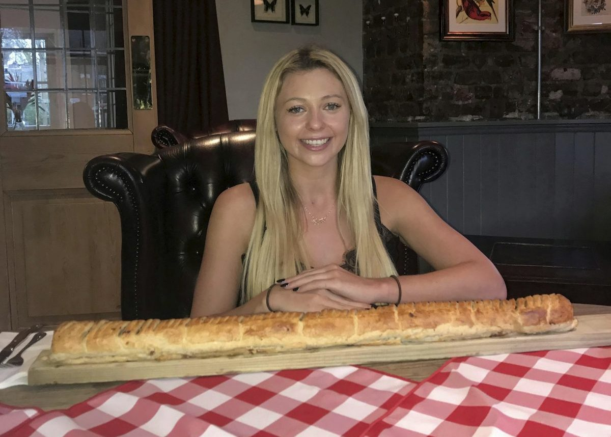 Kate Ovens begins her challenge to eat a saugsauge roll which is - three feet long. See National news story NNROLL; A woman has taken on Britain's biggest sausage roll - measuring a massive 3FT and so big it needs to be served on a FENCE POST. Famous challenge eater Kate Ovens managed to polish off most of the giant snack in just TEN minutes. But the 23-year-old feared she had met her match with the 3750-calorie snack - because she hit 'the wall' with less than six inches of the meaty treat left. The 5ft 5ins eating machine went for a tactical walk for about ten minutes in a bid to free up some more room.