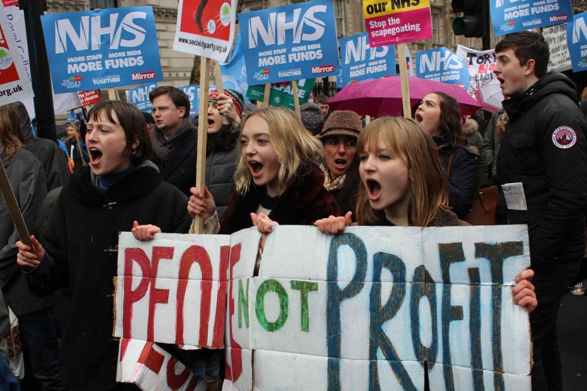 Three young activists hold a 'people not profit sign'