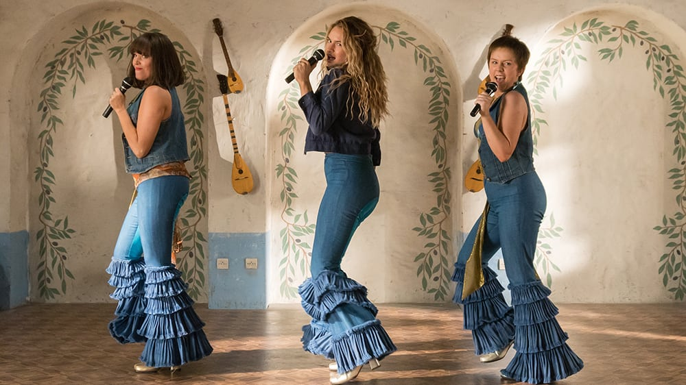 """(L to R) Young Tanya (JESSICA KEENAN WYNN), Young Donna (LILY JAMES) and Young Rosie (ALEXA DAVIES) in """"Mamma Mia! Here We Go Again.""""  Ten years after """"Mamma Mia! The Movie,"""" you are invited to return to the magical Greek island of Kalokairi in an all-new original musical based on the songs of ABBA."""