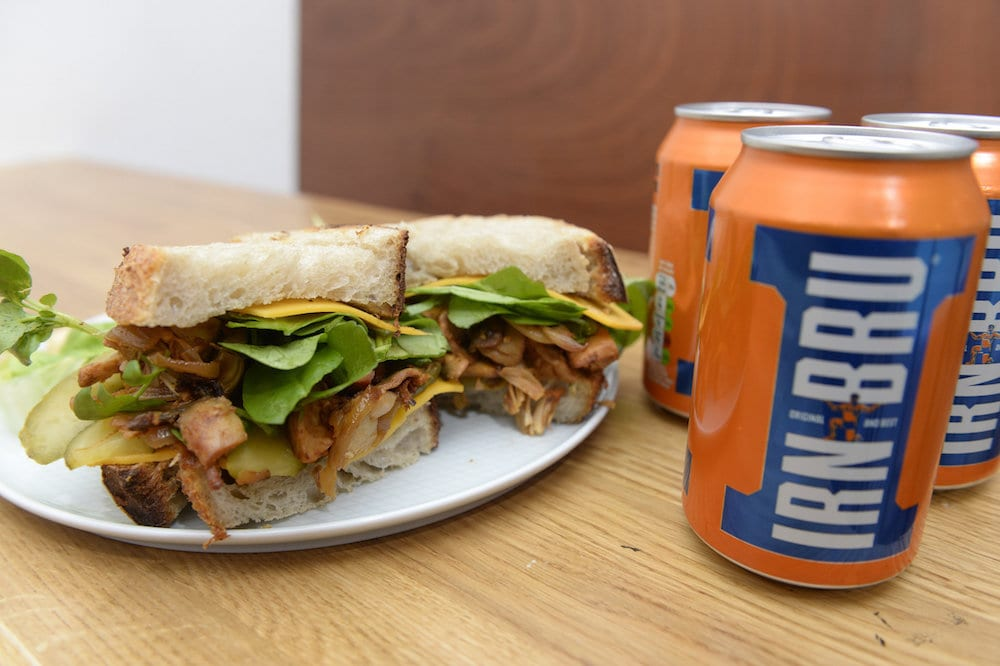 Cafe owner Amelia Sulhunt, from Serenity Now Cafe, Glasgow, Scotland, with a Vegan Irn Bru sandwich made from pulled Jackfruit. The Jackfruit is roasted after Irn Bru is poured on it.   See SWNS story SWSCsandwich; A family-run vegan cafe is set to make taste buds across the city explode with the launch of a new Irn Bru infused winter sandwich. Serenity Now Cafe will soon offer the juicy sandwich served on toasted sourdough bread with BBQ sauce, rocket, cheese and pickles. And the Irn Bru is roasted with pulled jackfruit and mushrooms in the barbecue sauce. The mouthful bite also comes with side-salad, air-fried chips or mac and cheese. Glaswegians have been flocking to try the £6.50 sandwich which will be sold at the cafe based at Great Western Rd, Glasgow.