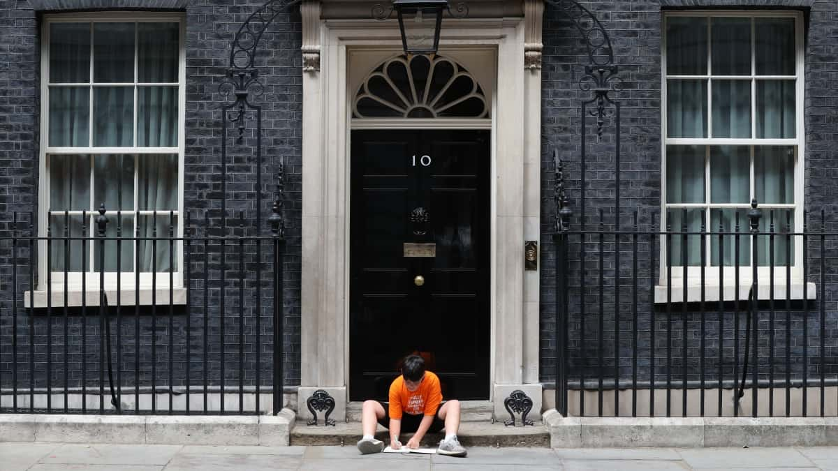Jess Phillips leaves her son outside No 10 to protest education cuts making school hours shorter (PA)