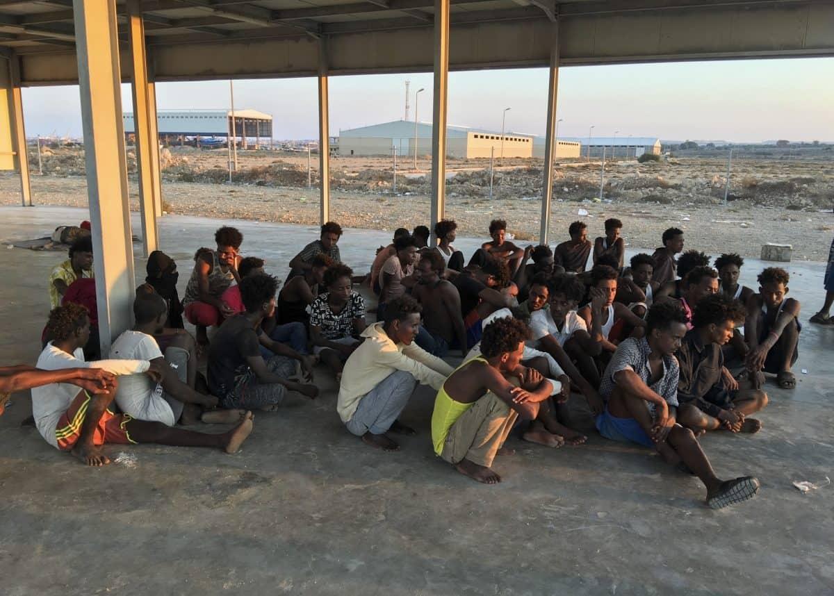 Rescued migrants sit on a coast (Hazem Ahmed/AP)