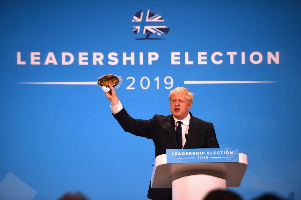 Johnson waves a kipper at Tory leadership hustings to make a point about EU regulations (PA)