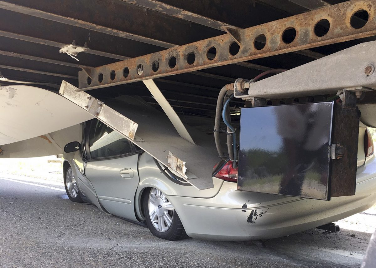 In this photo released Tuesday, July 16, 2019 by the Uxbridge Fire Department on its Facebook page, a car sits wedged under a tractor-trailer on Route 146 in Uxbridge, Mass. The motorist, whose name wasn't made public, climbed out of the driver's side door of the crushed car and wasn't seriously hurt. (Uxbridge Fire Department via AP)