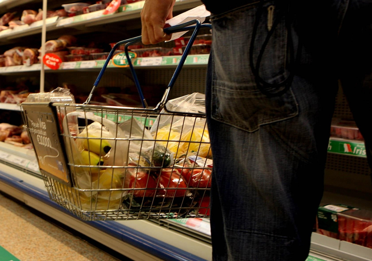 """Undated file photo of a man holding a shopping basket in a supermarket. The price of food and drink will """"go through the roof"""" if the UK leaves the EU without a deal, a new study suggests."""