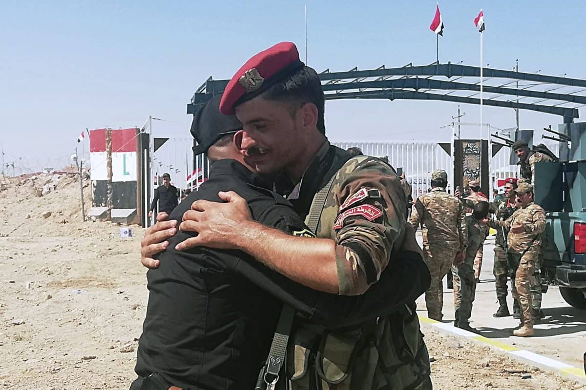 Iraq and Syria border guards soldiers congratulate each other during the opening ceremony of the crossing between the Iraqi town of Qaim and Syria's Boukamal in Anbar province, Iraq, Monday, Sept. 30, 2019. Iraq and Syria have opened a key border crossing between the two neighboring countries seven years after it was closed during Syria's civil war. (AP Photo/Hadi Mizban)