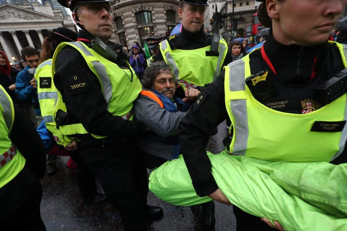 A protester is carried away by police as others block the road in front of the Bank of England (Gareth Fuller/PA)