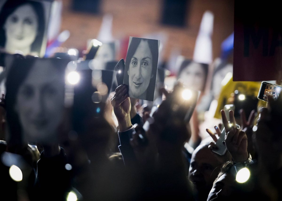People hold pictures of slain journalist Daphne Caruana Galizia as they protest outside the office of the Maltese Prime Minister Joseph Muscat, calling for the resignation of Muscat, in Valletta, Malta., Friday, Nov. 29, 2019. The family of the journalist who was killed by a car bomb in Malta is urging Muscat to resign, after his former chief aide was released from jail in a probe aimed at finding the mastermind of the 2017 murder. (AP Photo/Rene Rossignaud)