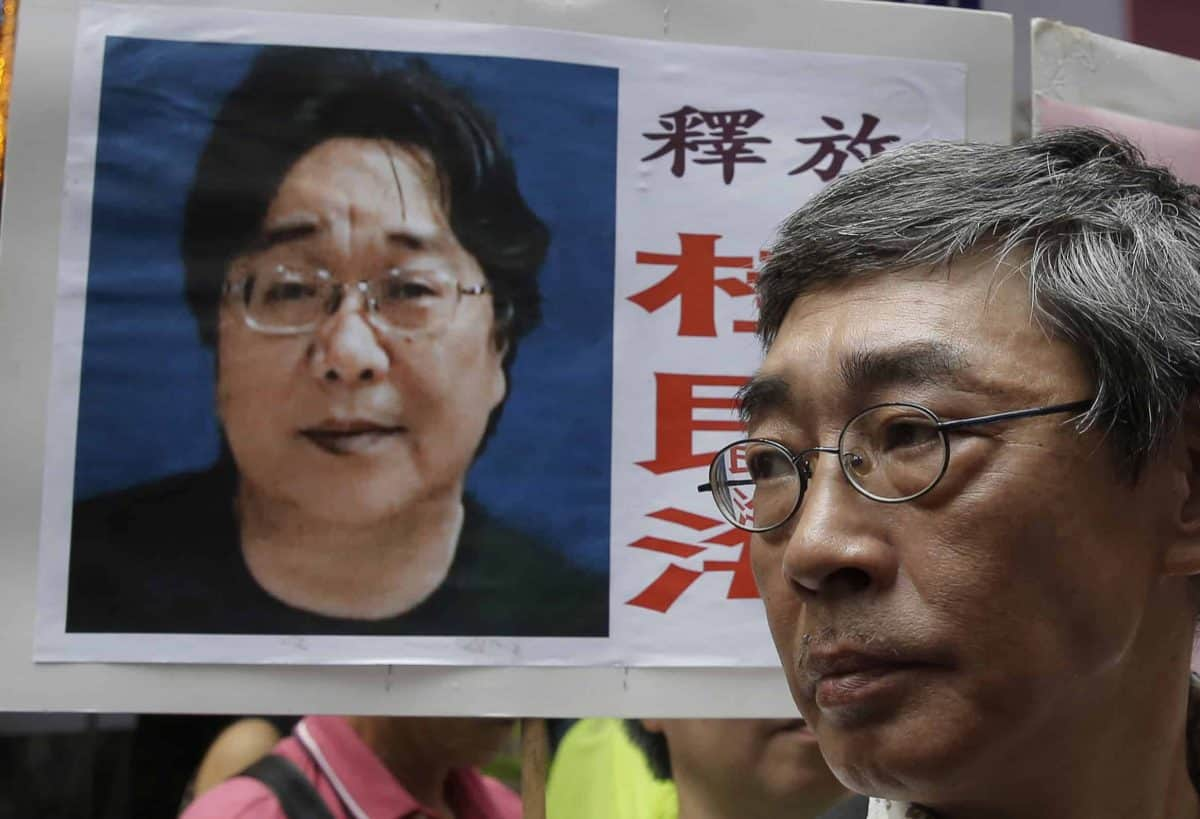 A picture of missing bookseller Gui Minhai is shown on a placard beside freed Hong Kong bookseller Lam Wing-kee, as the protesters are marching to the Chinese central government's liaison office in Hong Kong. A court in eastern China announced Tuesday, Feb. 25, 2020, that it has sentenced Gui, a naturalized Swedish citizen, to 10 years in prison. (AP Photo/Kin Cheung, File)