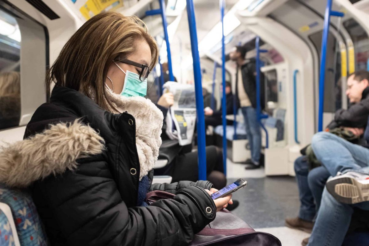 A woman wearing a facemask on the London Underground.