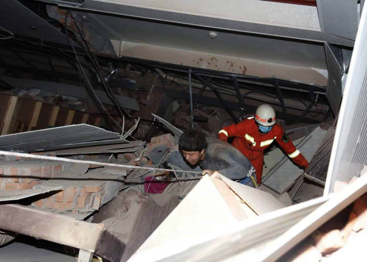 A man is assisted out from the rubble of a collapsed hotel building in Quanzhou city in southeast China's Fujian province Saturday, March 07, 2020. The hotel used for medical observation of people who had contact with coronavirus patients collapsed in southeastern China on Saturday, trapping dozens, state media reported. (Chinatopix via AP)
