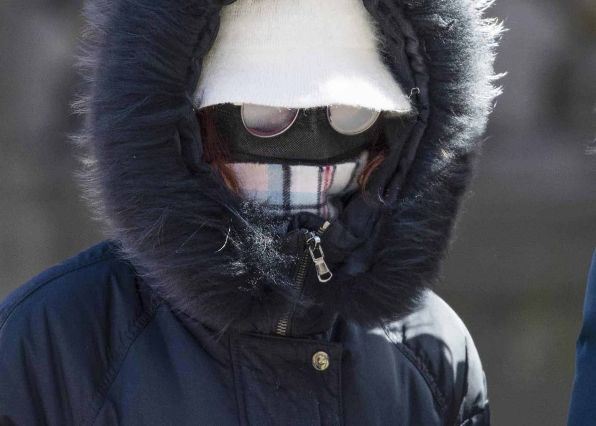 A woman wearing a protective face mask walks along the Royal Mile, Edinburgh, as the Government's top scientist warmed that up to 10,000 people in the UK are already infected.