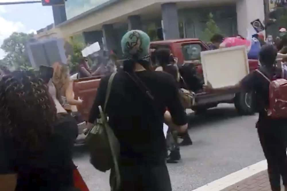 In this image taken from from video provided by @alexisnscott._, a pickup truck drives through a crowd of protesters, Saturday, May 30, 2020, in Tallahassee, Fla Tallahassee police said Saturday that the driver was in custody and that no one was seriously injured.  (@alexisnscott._ via AP)