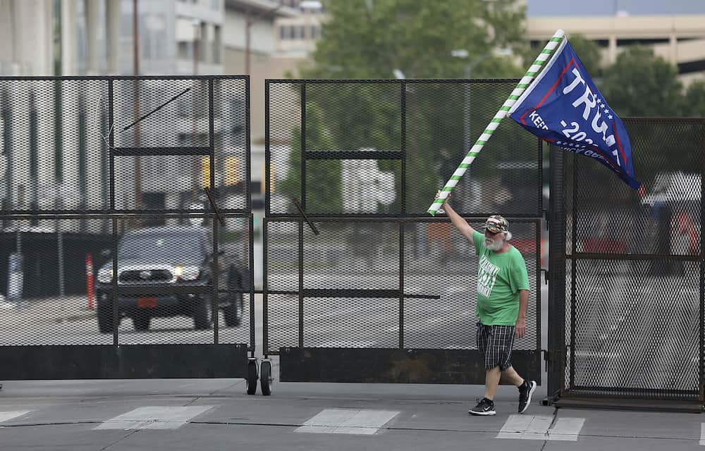 Mike Pellerin waves a Donald Trump campaign flag near a barricade after driving  all night from Austin, Tx. to line up and camp with other Trump supporters on 4th Street and Cheyenne Ave. in downtown Tulsa ahead of Saturday's campaign rally Friday, June 19, 2020. The area for several blocks around the BOK Center is barricaded. Upon arriving Pellerin said he needed to burn some energy before taking a nap. MIKE SIMONS/Tulsa World