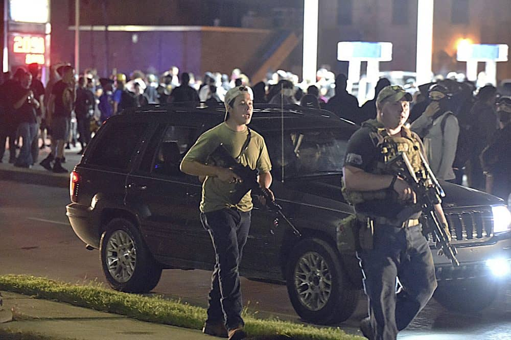 Kyle Rittenhouse, left, with backwards cap, walks along Sheridan Road in Kenosha, Wis., Tuesday, Aug. 25, 2020, with another armed civilian. Prosecutors on Thursday, Aug. 27, 2020 charged Rittenhouse, a 17-year-old from Illinois in the fatal shooting of two protesters and the wounding of a third in Kenosha, Wisconsin, during a night of unrest following the weekend police shooting of Jacob Blake. (Adam Rogan/The Journal Times via AP)