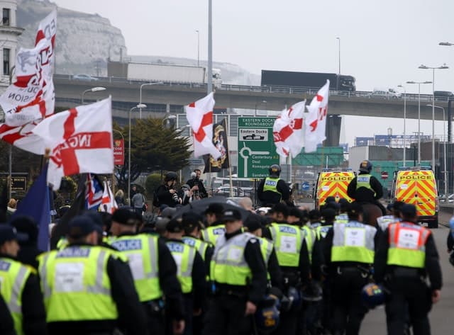 Police officers march with far-right protesters though Dover in Kent as they demonstrate against the arrival of immigrants in 2016 Credit;PA